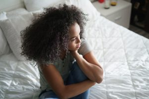 A girl with curly hair sitting on a bed and staring into the distance.