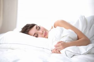 Brunette woman sleeping in white linens