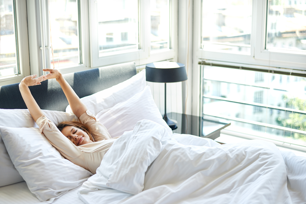 woman laying in bed stretching her arms up