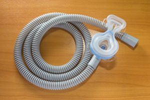 A CPAP mask and tube on a wood background