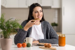 A woman eating toast in the kitchen with food around her