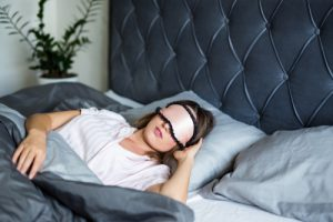 A woman sleeping in bed wearing an eye mask