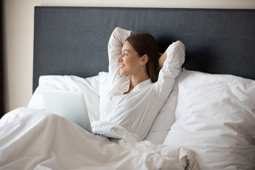 A person sitting up in bed with her arms behind her head and looking out the window