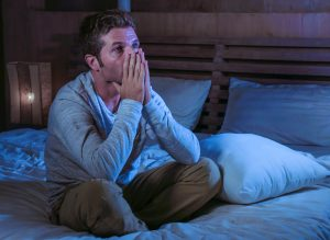 Stressed and anxious man on his bed at night