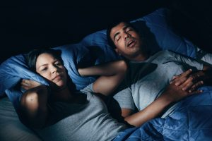 Annoyed woman lying in bed with snoring boyfriend at home in the bedroom