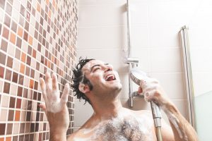 Young Caucasian man, singing and gesturing happily full of soap in the bathroom shower.